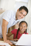 Man and young girl with laptop in dining room. Smiling stock photo