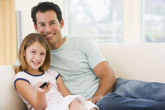 Man and young girl in living room with remote Stock Photography