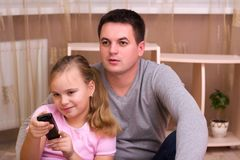 Man and young girl in living room with remote control smiling. Man and young girl in living room with remote control smiling royalty free stock images