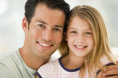 Man and young girl in living room smiling Stock Photo