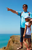Man and young girl standing in a beach sea. The man points to a Stock Photography