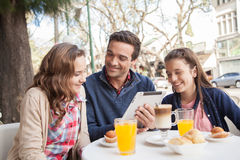Man and young girls using the tablet in the street Royalty Free Stock Photo