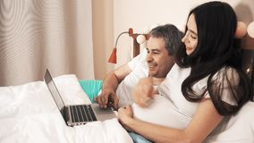 Man and young pregnant woman shopping online using their laptop in bed stock video footage