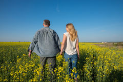 Man with a young smiling woman are walking through a field Royalty Free Stock Photo