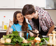 Man and young woman cooking together Stock Photography