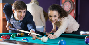 Man and young woman hit one ball in billiards Stock Images