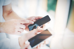 Man and young woman holding in hands their gadgets Stock Images
