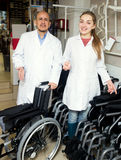 Man and young woman with mechanical wheelchairs. Mature men and happy women with mechanical wheelchairs in store Stock Photo