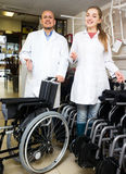 Man and young woman with mechanical wheelchairs. Mature men and young women with mechanical wheelchairs in store. Focus on the man Stock Photo