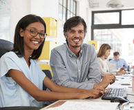 Man and young woman in open plan office looking to camera�. Man and young women in open plan office looking to camera Stock Image