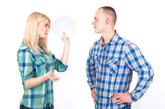 A man and a young woman with a plate in her hand quarrel in a studio. Royalty Free Stock Photo