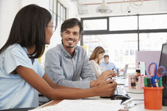 Man and young woman talking in a busy open plan office. Man and young women talking in a busy open plan office Stock Images