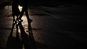 Man and young woman walking on a street. Couple holding hands on their date in a city street at early morning, shadows stock video