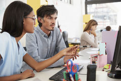 Man and young woman working together in an open plan office. Man and young women working together in an open plan office Royalty Free Stock Images