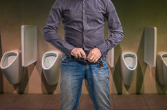 Man zip his pants up after peeing on the public toilet Royalty Free Stock Photos