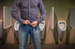 Man zip his pants up after peeing on the public toilet Stock Photo