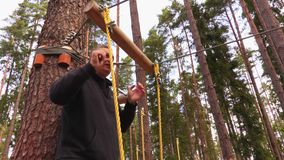 Man on zip line in forest. In summer day stock video footage