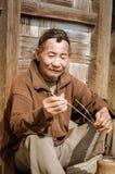 Man in Ziro in Arunachal Pradesh. Ziro, Arunachal Pradesh - circa March 2012: Photo of older man in brown shirt during weaving of basket in Ziro, Arunachal Royalty Free Stock Images