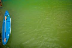 MANABI, ECUADOR - 4 DE JUNIO DE 2012: Pequeño barco del bue en el agua estancada con una máquina en lo mismo, Ecuador del bombeo  Imagen de archivo libre de regalías