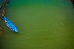MANABI, ECUADOR - 4 DE JUNIO DE 2012: Pequeño barco del bue en el agua estancada con una máquina en lo mismo, Ecuador del bombeo  Fotografía de archivo libre de regalías