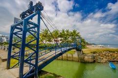 MANABI, EQUADOR - 4 DE JUNHO DE 2012: Ponte azul grande sobre um rio pequeno verde em mesmos, Equador, ponto de férias popular no Foto de Stock Royalty Free