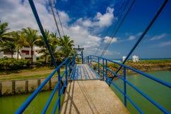 MANABI, EQUADOR - 4 DE JUNHO DE 2012: Ponte azul grande sobre um rio pequeno verde em mesmos, Equador, ponto de férias popular no Fotografia de Stock Royalty Free