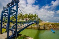 MANABI, EQUADOR - 4 DE JUNHO DE 2012: Ponte azul grande sobre um rio pequeno verde em mesmos, Equador, ponto de férias popular no Fotografia de Stock