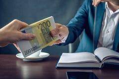 Manaffärsmannen i dräkt tar pengarhänderna En muta i form av euroräkningar Begrepp av korruption och bestickning arkivbilder