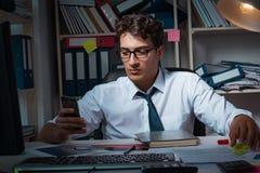 Manaffärsmannen som arbetar sena timmar i kontoret Fotografering för Bildbyråer