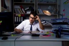 Manaffärsmannen som arbetar sena timmar i kontoret Arkivbilder