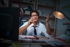 Manaffärsmannen som arbetar sena timmar i kontoret Arkivfoton