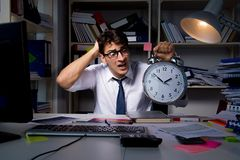 Manaffärsmannen som arbetar sena timmar i kontoret Arkivfoto