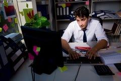 Manaffärsmannen som arbetar sena timmar i kontoret Arkivbild