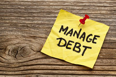 Manage debt reminder note. Manage debt - yellow reminder note against grained wood board stock images