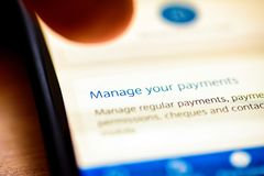 Manage payments button on smartphone app screen closeup with human finger pointing to it.  royalty free stock photography