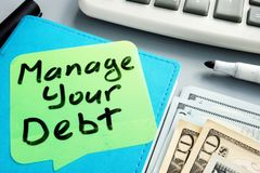 Manage your debt sign. Book and cash. Manage your debt sign. Note pad and cash royalty free stock photos
