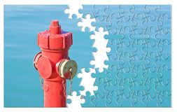 Manage your fire prevention plan - Red fire hydrant against a wa. Ter background - concept image in jigsaw puzzle shape stock images
