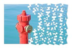 Manage your fire prevention plan - Red fire hydrant against a wa. Ter background - concept image in jigsaw puzzle shape royalty free stock images
