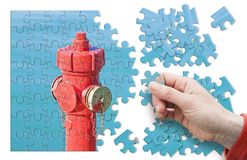 Manage your fire prevention plan - Red fire hydrant against a wa. Ter background - concept image in jigsaw puzzle shape stock photos