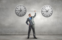 Manage your time. Confident businessman lifting above head barbell with clock Stock Image