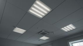 Managed on and off light in office room. Managed on and off light in the office. Fluorescent lamps on the ceiling stock footage