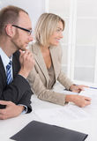 Management: Geschäftsteam, das am Schreibtisch in einer Sitzung sitzt lizenzfreie stockfotografie
