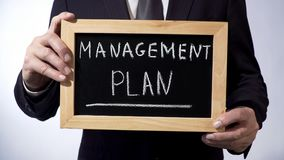 Management plan written on blackboard, business person holding sign, strategy Stock Images