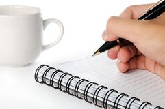 Management and recording of notes. A hand holding a pen ready to record notes Stock Photo