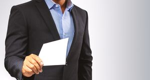 Management submits an envelope to employees.  stock photos