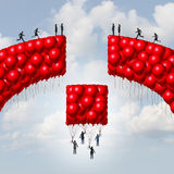 Management Team. Business concept as a group of balloons shaped as a broken bridge with leaders rising up with a balloon collection bridging the gap as a Royalty Free Stock Photography