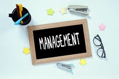 MANAGEMENT word on top view of blackboard with glasses, pen case, staplers and marker royalty free stock image