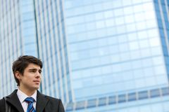 Manager. Handsome young entrepreneur on background of blue building outside Royalty Free Stock Images