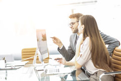 Manager and accountant are sitting and discussing financial charts with profits and expenditures of the company Stock Image