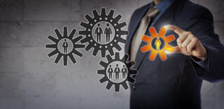 Manager Adding Female To An Efficient Work Team. Blue chip manager is adding a cog encircling a female employee to a gear train of white collar workers. Business royalty free stock image